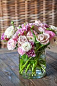 THE COACH HOUSE,SURREY: DETAIL OF FRESH RANUNCULUS, ROSES AND TULIPS IN VASE ON COFFEE TABLE. PRETTY, DECORATIVE, DISPLAY, ARRANGEMENT.