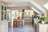 THE COACH HOUSE,SURREY:KITCHEN BY PLAIN ENGLISH, STOOLS FROM POTTERY BARN WITH BLUE LIMESTONE WORKTOPS.NEUTRAL DECOR,LIGHT,AIRY, TUMBLED MARBLE FLOOR, BELFAST/BUTLER SINK