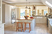 THE COACH HOUSE,SURREY:COUNTRY KITCHEN BY PLAIN ENGLISH, STOOLS FROM POTTERY BARN WITH BLUE LIMESTONE WORKTOPS.NEUTRAL DECOR,LIGHT,AIRY, TUMBLED MARBLE FLOOR, BELFAST/BUTLER SINK
