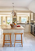 THE COACH HOUSE,SURREY: COUNTRY KITCHEN BY PLAIN ENGLISH,STOOLS FROM POTTERY BARN. NEUTRAL DECOR,LIGHT,AIRY,TUMBLED MARBLE FLOOR,BELFAST/BUTLER SINK, AGA,ISLAND