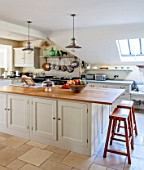 THE COACH HOUSE,SURREY: COUNTRY KITCHEN BY PLAIN ENGLISH, STOOLS FROM POTTERY BARN.NEUTRAL DECOR,LIGHT,AIRY, AGA, METAL PENDANT LIGHTS OVER ISLAND, TUMBLED MARBLE FLOOR