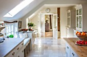 THE COACH HOUSE,SURREY: COUNTRY KITCHEN BY PLAIN ENGLISH, WITH BLUE LIMESTONE WORKTOPS AND ISLAND.NEUTRAL DECOR,LIGHT,AIRY, TUMBLED MARBLE FLOOR, WINDOW SEAT.