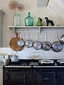 THE COACH HOUSE,SURREY: THE KITCHEN WITH DETAIL OF SHELF WITH HANGING POTS AND PANS ABOVE BLACK AGA. DECORATIVE, COUNTRY KITCHEN.