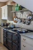 THE COACH HOUSE,SURREY: COUNTRY KITCHEN WITH BLACK AGA AND TILED SPLASHBACK WITH SHELF AND HANGING POTS AND PANS. NEUTRAL DECOR