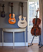THE COACH HOUSE,SURREY: DEMI LUNE TABLE FROM CHELSEA TEXTILES WITH MUSICAL INSTRUMENTS: ACOUSTIC GUITARS AND CELLO