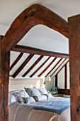 THE COACH HOUSE,SURREY: BEDROOM WITH DETAIL OF WOODEN BEAMS. CUSHIONS AND BED COVER BY HUDSON HOMES & INTERIORS. SIDE TABLE BY OKA