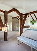 THE COACH HOUSE,SURREY: BEDROOM WITH OAK FRAME AND BENCH BY CHELSEA TEXTILES. NEUTRAL DECOR AND CARPET