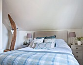THE COACH HOUSE,SURREY: GUEST BEDROOM - BLANKET FROM NEPTUNE, CUSHIONS FROM HUDSON HOMES & INTERIORS. NEUTRAL DECOR. OAK BEAM SUPPORT WITH HANGING HEART.