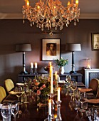 THE COACH HOUSE,SURREY: DINING ROOM. CHANDELIER BY INDIA JANE,CONSOLE TABLE & LAMPS BY MARGARET BOYD, DARK WOOD TABLE & FABRIC CHAIRS FROM HUDSON HOMES & INTERIORS.ENTERTAINING.
