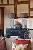 THE COACH HOUSE,SURREY: FAMILY ROOM WITH CHEST OF DRAWERS FROM THREE GATES GALLERY, LAMPS BY OKA. CUSHIONS ON SOFA BY CHELSEA TEXTILES.