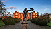 BURTON AGNES HALL, EAST YORKSHIRE: CHRISTMAS - LEAD BORGHESE GLADIATOR STATUE, YEW TOPIARY, DAWN, SUNRISE, DECEMBER, ORNAMENT, GARDEN, ENGLISH, CLASSIC, FORMAL