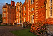 BURTON AGNES HALL, EAST YORKSHIRE: CHRISTMAS - FRONT OF ELIZABETHAN HALL AT SUNRISE, DAWN, HYDRANGEA MACROPHYLLA. HOUSE, MORNING LIGHT, CLASSIC, ENGLISH, GARDEN, FORMAL