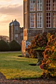 BURTON AGNES HALL, EAST YORKSHIRE: CHRISTMAS - ELIZABETHAN HALL  AND GATEHOUSE AT SUNRISE, DAWN, HYDRANGEA MACROPHYLLA. HOUSE, MORNING LIGHT, CLASSIC, ENGLISH, GARDEN, FORMAL