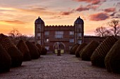 BURTON AGNES HALL, EAST YORKSHIRE: CHRISTMAS - THE GATEHOUSE AT SUNRISE - MORNING LIGHT, YEW, TAXUS BACCATA, CLIPPED, TOPIARY, DRIVEWAY, FAIRY LIGHTS, CLASSIC, FORMAL