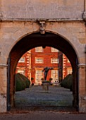 BURTON AGNES HALL, EAST YORKSHIRE: CHRISTMAS - THE ELIZABETHAN HOUSE SEEN THROUGH THE GATEHOUSE - YEW, TAXUS BACCATA, TOPIARY, MORNING, SUNRISE