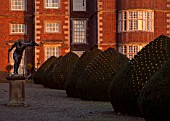 BURTON AGNES HALL, EAST YORKSHIRE: CHRISTMAS - 18TH CENTURY LEAD BORGHESE GLADIATOR LEAD STATUE ON ENTRANCE DRIVE - YEW TOPIARY, FAIRY LIGHTS, SUNRISE, DAWN