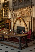 BURTON AGNES HALL, EAST YORKSHIRE: CHRISTMAS  - GREAT HALL, LONG OAK TABLE DECORATED WITH BRANCHES AND GOLDEN HOP - 18TH CENTURY CARVED CHIMNEY PIECE, ORNAMENT