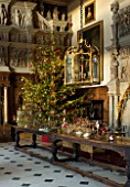BURTON AGNES HALL, EAST YORKSHIRE: CHRISTMAS  - GREAT HALL, LONG OAK TABLE DECORATED WITH BRANCHES AND GOLDEN HOP - 18TH CENTURY CARVED CHIMNEY PIECE, ORNAMENT, CHRISTMAS TREE