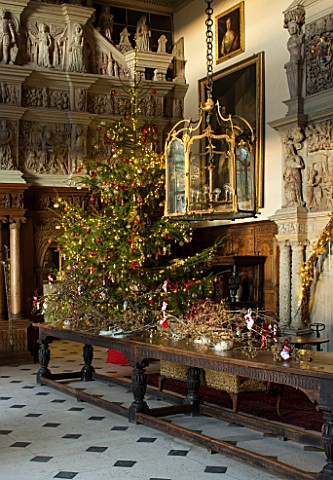 BURTON_AGNES_HALL_EAST_YORKSHIRE_CHRISTMAS___GREAT_HALL_LONG_OAK_TABLE_DECORATED_WITH_BRANCHES_AND_G