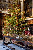 BURTON AGNES HALL, EAST YORKSHIRE: CHRISTMAS  - GREAT HALL, LONG OAK TABLE DECORATED WITH BRANCHES AND GOLDEN HOP - ORNAMENT, CHRISTMAS TREE