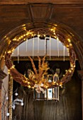 BURTON AGNES HALL, EAST YORKSHIRE: CHRISTMAS  - GREAT HALL - DRIED VINE WREATH DECORATED WITH GOLDEN FERNS AND FAIRY LIGHTS, MADE BY THE GARDENERS. ORNAMENT