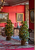 BURTON AGNES HALL, EAST YORKSHIRE: CHRISTMAS - THE DINING ROOM WITH BAY TREES. LAURUS NOBILIS, PORTRAIT OF OLIVER CROMWELL. RED, LIGHTS, LIGHTING