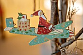 BURTON AGNES HALL, EAST YORKSHIRE: CHRISTMAS - THE GARDEN GALLERY - WOODEN AEROPLANE CUT OUT DECORATION IN OAK TREE. ORNAMENT, DECORATION