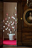 BURTON AGNES HALL, EAST YORKSHIRE: CHRISTMAS - THE JUSTICES ROOM - A SYCAMORE BRANCH DECORATED WITH PAPER SNOWFLAKES AND HAND KNITTED STOCKINGS