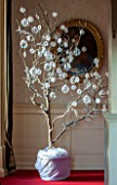 BURTON AGNES HALL, EAST YORKSHIRE: CHRISTMAS - THE MUSIC GALLERY - A SYCAMORE BRANCH DECORATED WITH FROSTED BAUBLES AND CROCHET WORK DECORATIONS