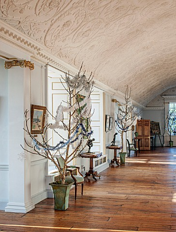 BURTON_AGNES_HALL_EAST_YORKSHIRE_CHRISTMAS__THE_LONG_GALLERY__WALNUT_TREE_BOUGHS_IN_METAL_PLANTERS_D
