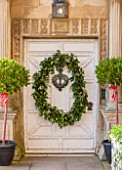 BURTON AGNES HALL, EAST YORKSHIRE: CHRISTMAS - WHITE FRONT DOORWAY WITH BAY TREES IN BLACK CONTAINERS, HOLLY AND BERRY WREATH MADE BY THE GARDENERS WITH PLANTS FROM ESTATE