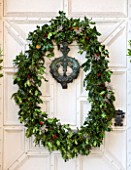 BURTON AGNES HALL, EAST YORKSHIRE: CHRISTMAS - WHITE FRONT DOORWAY WITH HOLLY AND BERRY WREATH MADE BY THE GARDENERS WITH PLANTS FROM ESTATE