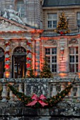 VAUX LE VICOMTE, FRANCE: THE ENTRANCE TO THE PALACE AND MOAT BALLUSTRADE AT CHRISTMAS DECORATED WITH RIBBON BOWS AND CHRISTMAS TREES. TREE, LIGHT, LIGHTING, ILLUMINATION, WINTER