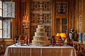 VAUX LE VICOMTE, FRANCE: THE GAMES PARLOUR DECORATED FOR CHRISTMAS. THE CENTRAL TABLE IS SET WITH A MAGNIFICENT TIERED CAKE, BRANDY SNAP BOWLS, MACAROONS, CREAM HORNS AND FRUITS