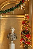 VAUX LE VICOMTE, FRANCE: THE ENTRANCE HALL DECORATED FOR CHRISTMAS. A BUST SITS BESIDE SEASONAL SWAGS AND DECORATIONS