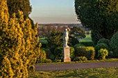BRODSWORTH HALL, YORKSHIRE: VIEW ACROSS LAWN TO BORDER OF TOPIARY. VICTORIAN, COUNTRY, GARDEN, FORMAL, STATUARY, STATUES, STATUE, CLIPPED, COUNTRYSIDE, EVENING