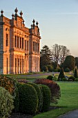 BRODSWORTH HALL, YORKSHIRE: SUNRISE - VIEW ACROSS LAWN TO BORDER OF CLIPPED EVERGREEN TOPIARY WITH HALL BEHIND. VICTORIAN, COUNTRY, GARDEN