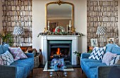 THE FREETH, HEREFORDSHIRE: THE SITTING ROOM. FIRE, FIREPLACE, BOOKCASE WALL PAPER, TEAL SOFAS, WOOD FLOOR, GLASS AND STONE PEDESTAL TABLE, GILT MIRROR, LIVING, ROOM