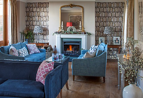 THE_FREETH_HEREFORDSHIRE_THE_SITTING_ROOM_FIRE_FIREPLACE_BOOKCASE_WALL_PAPER_TEAL_SOFAS_WOOD_FLOOR_G