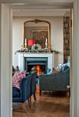 THE FREETH, HEREFORDSHIRE: THE SITTING ROOM. FIRE, FIREPLACE, BOOKCASE WALL PAPER, TEAL SOFAS, WOOD FLOOR, GILT MIRROR, LIVING, ROOM