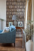 THE FREETH, HEREFORDSHIRE: THE SITTING ROOM. BOOKCASE WALL PAPER, TEAL SOFA, WOOD FLOOR, GLASS AND NICKEL LAMP, LIVING