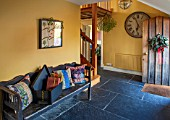 THE FREETH, HEREFORDSHIRE: HALLWAY - SLATE TILES, SLABS, SWEDISH WOODEN BENCH, PRINT ROOM YELLOW FROM FARROW AND BALL PAINTED WALLS, CLOCK, CUSHIONS