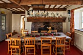 THE FREETH, HEREFORDSHIRE: KITCHEN, DINER - WOODEN FARMHOUSE TABLE, SCHOOL, CHURCH CHAIRS, GOLDEN ANTIQUE ANGEL CANDLE HOLDERS, FIREPLACE, RED FLOORING