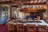 THE FREETH, HEREFORDSHIRE: KITCHEN, DINER - WOODEN FARMHOUSE TABLE, SCHOOL, CHURCH CHAIRS, GOLDEN ANTIQUE ANGEL CANDLE HOLDERS, FIREPLACE, RED FLOORING, BLUE GLASS CUPBOARD