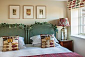 THE FREETH, HEREFORDSHIRE: GREEN AND RUBY BEDROOM. RATAN BEDHEADS, SHOE PRINT CUSHIONS, THROW, TULIP PRINT BLIND, LAMP AND SHADE