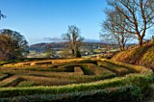PAINSWICK ROCOCO GARDEN, GLOUCESTERSHIRE: VIEW ACROSS MAZE TO COUNTRYSIDE BEYOND. HEDGE, HEDGES, HEDGING, JANUARY, WINTER