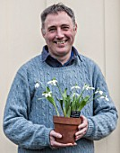 HILL CLOSE GARDENS, WARWICK: HEAD GARDENER GARY LEAVER HOLDING SNOWDROPS IN TERRACOTTA CONTAINER - GALANTHUS, MAN