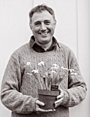 HILL CLOSE GARDENS, WARWICK: BLACK AND WHITE IMAGE OF HEAD GARDENER GARY LEAVER HOLDING SNOWDROPS IN TERRACOTTA CONTAINER - GALANTHUS, MAN