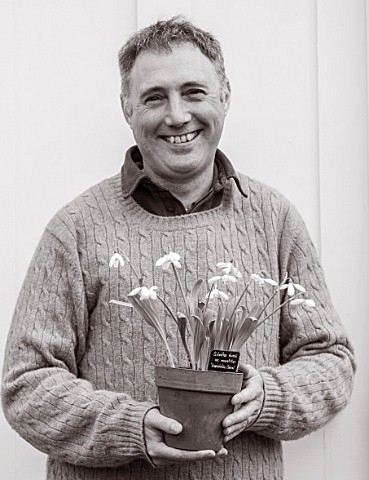 HILL_CLOSE_GARDENS_WARWICK_BLACK_AND_WHITE_IMAGE_OF_HEAD_GARDENER_GARY_LEAVER_HOLDING_SNOWDROPS_IN_T