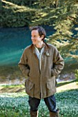 COLESBOURNE PARK, GLOUCESTERSHIRE: HEAD GARDENER ARTHUR COLE BY THE LAKE WITH SNOWDROPS